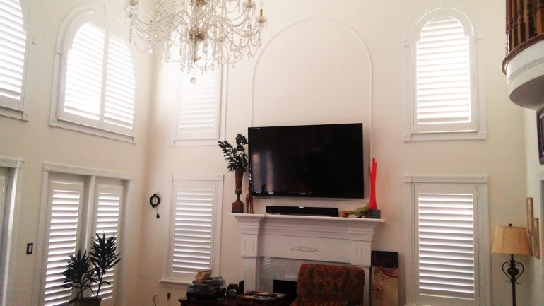 Gainesville great room with mounted television and high-ceiling windows.